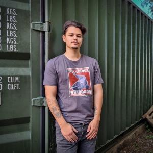 Max am Peuter Elbdeich in Hamburg trägt unser Ahoi Plünn Fishing T-Shirt 'Wels in der Brandung, front