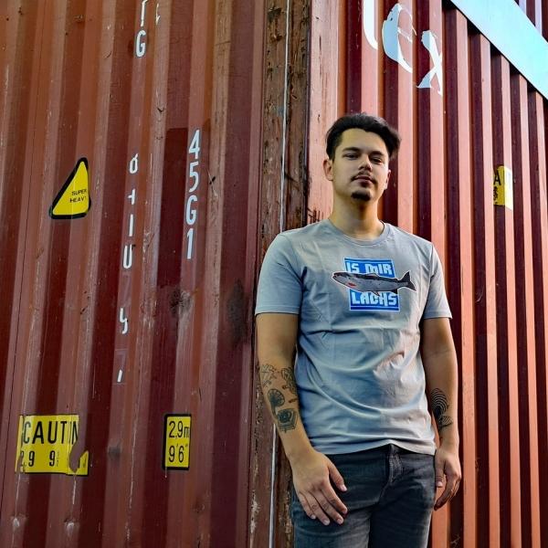 Max trägt das Ahoi Plünn Fishing T-Shirt Is mir Lachs und steht vor einem Container